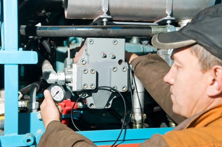 maintenance engineer: serviceman repairman measuring the pressure with manometer