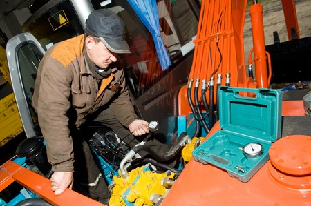 serviceman: serviceman repairman checking hydraulic pressure by measuring it with manometer