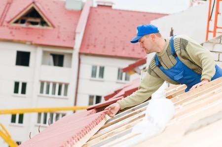 builder worker laborer at roofing tiling works photo