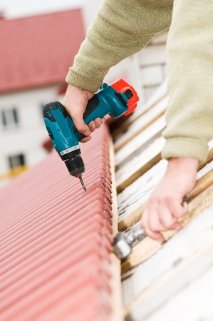 Hands of builder worker at roofing works on tiling with screwdriver Stock Photo - 8202905