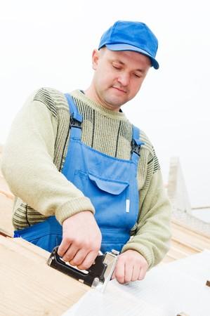 staple gun: builder worker at roofing works on tiling with staple gun