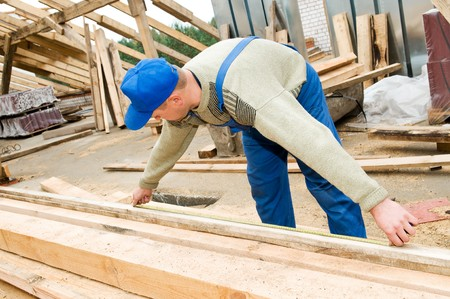 trussing: builder worker at roofing works measuring length of wood timber with measuring tape Stock Photo