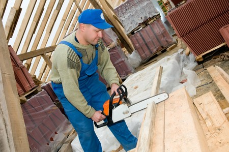 builder worker at roofing works cutting wood timber with po�table saw photo