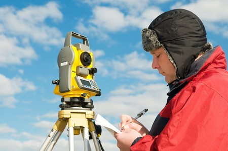 exact position: One surveyor worker with theodolite equipment outdoors writing the data Stock Photo