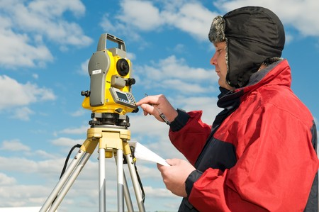 exact position: One surveyor worker with theodolite equipment outdoors input the data
