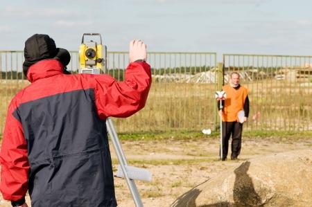 encuestando: Dos trabajadores de topógrafo con equipos de teodolito al aire libre  Foto de archivo