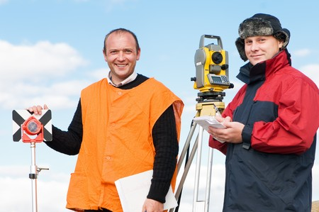 Two happy surveyor workers with theodolite equipment photo