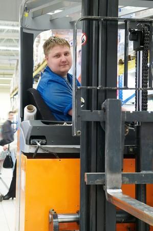 Worker driver of a forklift loader in blue workwear at warehouse photo