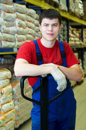 warehouse equipment: young handsome warehouse worker man in front of stack arrangement of goods
