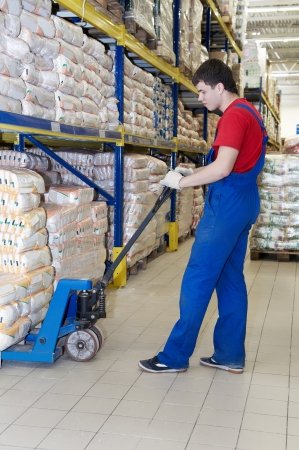 food distribution: worker with fork pallet truck stacker in warehouse loading Group of food packages