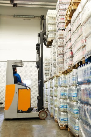 Worker driver of a forklift loader at warehouse picking up load on pallet to stockpile photo