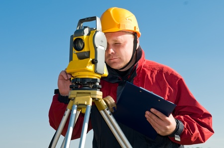 theodolite: Surveyor worker making measurement in a field with theodolite total station equipment