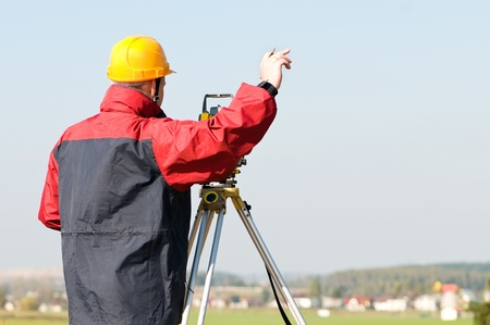 exact position: Surveyor worker making measurement in a field with theodolite total station equipment
