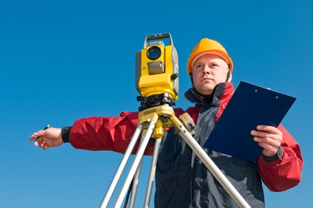 tacheometer: Surveyor worker making measurement in a field with theodolite total station equipment