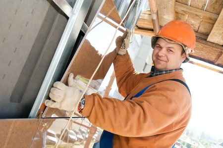 scaffolds: One happy construction worker builder installing big tile on a building facade