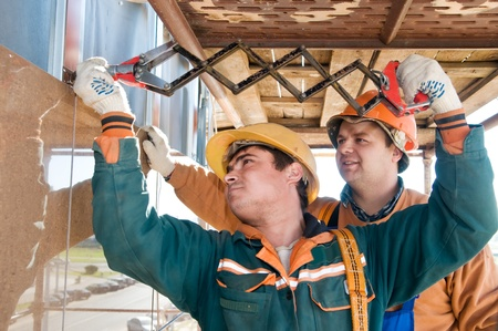 cladding tile: Two construction workers builders riveting big tile on a building facade   Stock Photo