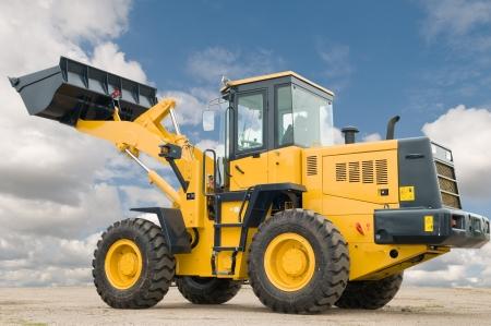 maquinaria: Un cargador de excavadora maquinaria maquinaria de construcci�n sobre el cielo azul