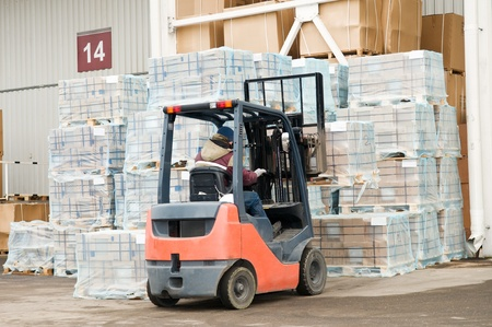 forklift loader at warehouse outdoors stacking cardboard boxes on pallet to stockpiles photo