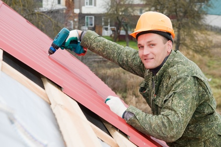 builder worker at roofing works on metal tiling with screwdriver photo