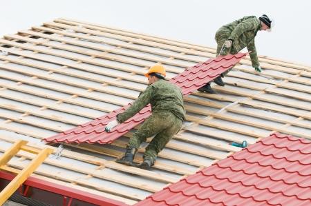 shingles: dos trabajadores en techo en obras con baldosas de metal y hierro de techos