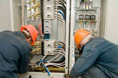maintenance engineer: Two electricians working on a industrial panel mounting and assembling new wiring