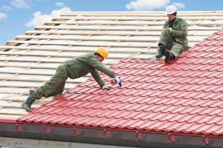 trussing: two workers on roof at works with metal tile and roofing iron Stock Photo
