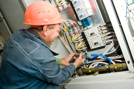 One electrician working on a industrial panel mounting and assembling new wiring photo