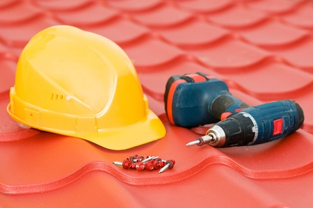 roofer: Metal roof tile with hardhat, hardware and screwdriver. Shallow depth of view. Focus on screws. Stock Photo