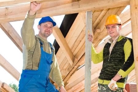 trussing: gruppo di carpentieri roofers lavoratori in uniforme alle coperture funziona con livello Archivio Fotografico