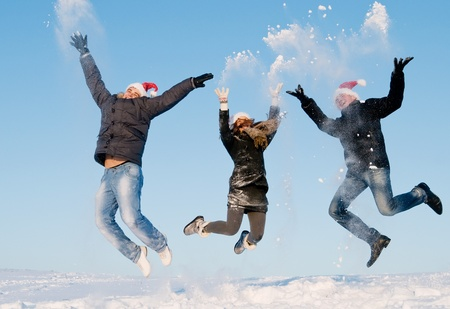 happy young people jumping with snow splashes in winter air photo