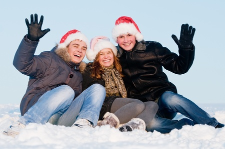 happy young cheerful people sitting in snow at winter outdoors photo