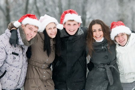 five jolly young boys and girls embracing each other on shoulders wearing red hat at snowy winter outdoors photo