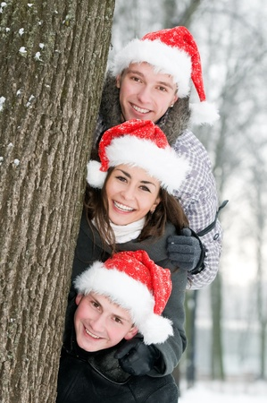 three cheerful young people in rad hats outdoors photo