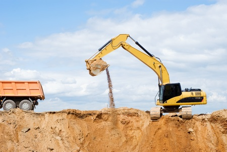 Loader Excavator loading body of a dump truck tipper at open cast over blue sky in summer photo
