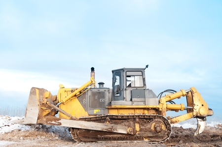 ripper: Heavy bulldozer loader at winter frozen soil ripping, moving and excavation works in sandpit