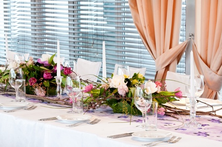 catering table: catering table set service with silverware, fresh flowers and glass at restaurant before party