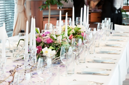 wedding table setting: catering table set service with silverware, fresh flowers and glass at restaurant before party