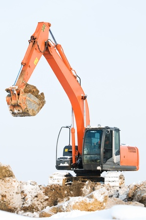 sand quarry: Heavy excavator loader at winter frozen soil moving works in sandpit Stock Photo