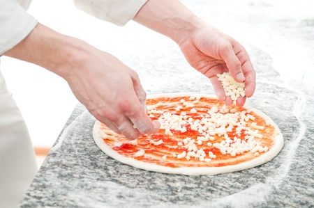 Closeup hand of chef baker in white uniform making pizza at kitchen photo