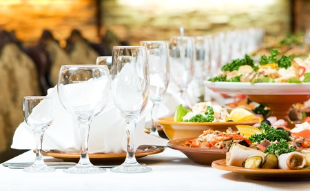 food and drink industry: catering table set service with silverware and glass stemware at restaurant before party Stock Photo