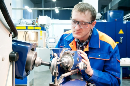 Worker in uniform and protective glasses sharpen countersink reamer at machine tool photo