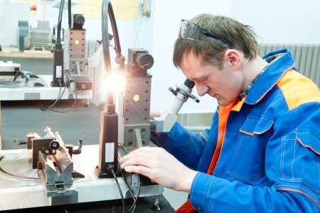 precise: Worker in uniform checking quality of countersink reamer sharpening using precise optical device Stock Photo
