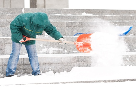 digging: communal services worker in uniform shoveling snow in winter snowstorm Stock Photo