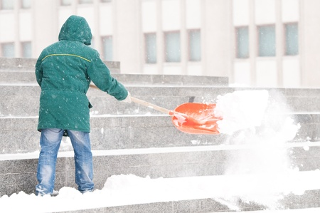 winter storm: communal services worker in uniform shoveling snow in winter snowstorm Stock Photo