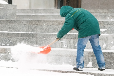 communal: communal services worker in uniform shoveling snow in winter snowstorm Stock Photo