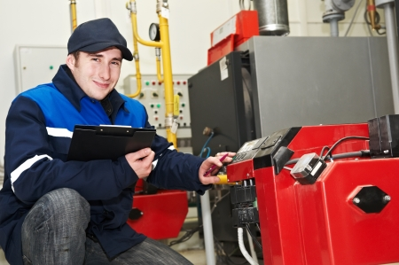 repairmen: heating engineer repairman in boiler room Stock Photo