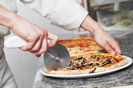 bakery oven: Pizza preparartion - cutting Stock Photo