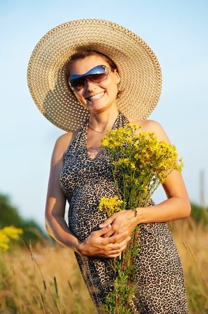 Pregnant smiling woman in field Stock Photo - 10366784