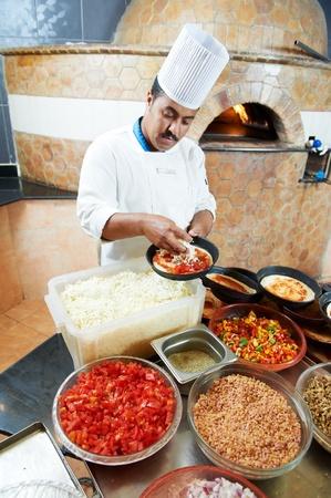Arab baker chef making Pizza photo
