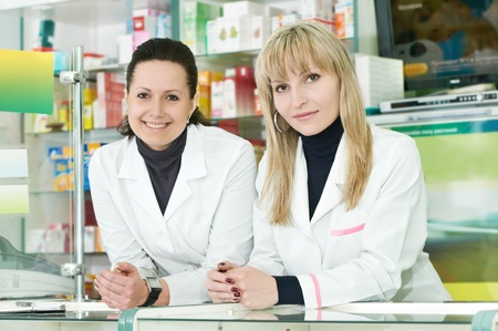 Two Pharmacy chemist women in drugstore photo